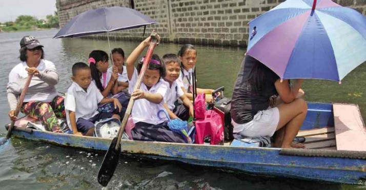 PADDLING TO SCHOOL Pupils take a makeshift boat going to Panghulo Elementary School in flood-plagued Malabon City on the first day of classes. The short ride costs them P5 each. MARIANNE BERMUDEZ